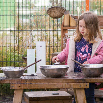 girl in mud kitchen cooking